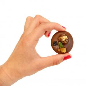 mendiant au chocolat lait tenu dans une main